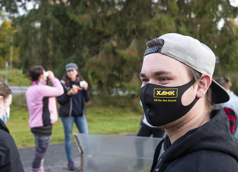 Kuvassa on nuori mies lippis väärinpäin päässä. Hänellä on naamansa suojana Xamk-kasvomaski. Hän hymyilee. Taka-alalla seisoo ihmisiä.