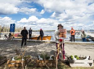 Kuvassa poseeraa kuusi ihmistä Anttolan satamassa. Heidän takanaan on sininen taivas ja veneitä.