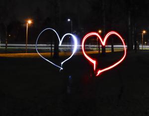 Kuva on tumma. Kuvan keskelle ilmaan on piirretty valolla sininen ja punainen sydän.