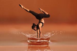 Kuvassa nainen seisoo käsillään, jalat balettimaiseen asentoon taipuneena. Kädet iskevät veden pinnasta isot roiskeet.