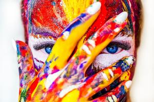 Kuvassa naisen kasvot, joita peittää käsi. Sekä kasvot että kädet ovat värikkäät, ikään kuin maaliroiskeita ja -jälkiä täynnä.
