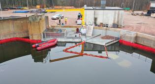 Kuvassa näkyy suuri vesiallas, jossa voi harjoitella öljyntorjuntaa. Kuvassa näkyy muun muassa kumivene, öljyntorjuntapuomeja ja veden pinnan alla oleva auto.