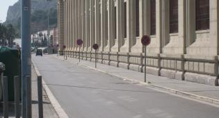 Kuvassa näkyy maisema kaupungista. Virastomaisen talon edessä on asfaltoitu katu, jossa jonossa ainakin kuusi pysähtymiskieltoa osoittavaa liikennemerkkiä.