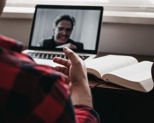 Kuvassa näkyy henkilö, joka on selin ja hänestä näkyy vain oikea olkapää ja osa oikeaa kättä. Henkilöä vastapäätä on pöydällä kirja ja tietokone, jonka näytöllä näkyy hymyilevän henkilön kasvot.