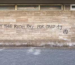 Kuvassa vaaleanruskea tiiliseinä, johon on kirjoitettu teksti: Let the rich pay for covid 19.