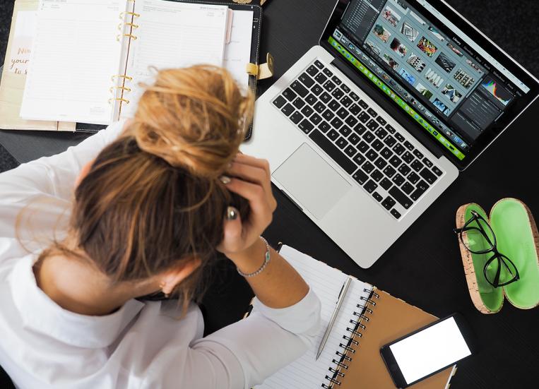 Kuvassa näkyy nuori nainen, joka on pää painuksissa ja nojaa käsiinsä. Hänen edessään pöydällä on auki oleva tietokone, avoinna olevia vihkoja, silmälasikotelo ja silmälasit sekä matkapuhelin.
