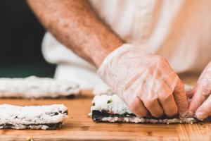 Kuvassa kokin kädet tekemässä sushia.