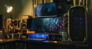 Kuvassa näkyy pelien kehittämiseen ja tietotekniikkaan liittyviä laitteita kuten tietokoneen keskusyksikkö, isoja näyttöjä, kaiuttimia.