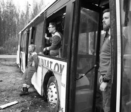 Mustavalkoisessa kuvassa näkyy linja-auto, joka ilmeisimmin on ollut onnettomuudessa. Linja-autoon nojaa yksi ensihoitaja, yksi ensihoitaja katsoo linja-auton ikkunasta ja yksi ovesta.