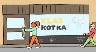 Kuvassa näkyy sarjakuvan ruutu, jossa näkyy Xlab Kotkan ulkonäkymä kadulta päin. Tilaa kohti kävelee kaksi sarjakuvahahmoa, nainen ja mies. Naisen käsi on jo oven kahvassa, mies kävelee iloisena kohti ovea.