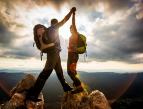 Kuvassa näkyy mies ja nainen, molemmat ovat vuoren huipulla ja pitävät toisiaan kädestä kiinni. Kädet ovat ylhäällä kohotettuna kohti taustalla näkyvää auringonvaloa. Taustalla näkyy myös maisema alas laaksoon.