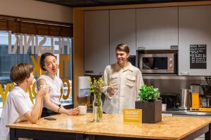 Kuvassa Helsinki Think Companyn tiloissa oleva keittiö, jossa on kolme iloista opiskelijaa juomassa kahvia ja keskustelemassa.