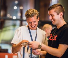 Kuvassa näkyy kaksi nuorta miestä. Oikealla oleva nuori mies nauraa ja pitää kädessään *ship-tapahtuman kulkupassia. Vasemmalla oleva nuori osoittaa passia sormellaan ja nauraa.