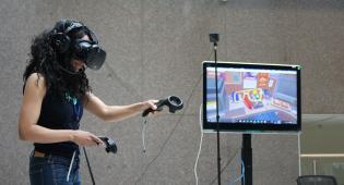 Ihminen kokeilee virtuaalilaseja ja käsien liikkeen tunnistavia sensoreita.