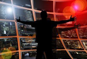 Kuvassa näkyy tumma miehen hahmo. Hänen edessään on videoseinä, jossa on lukemattomia ruutuja tai ikkunoita, joista jokaisesta aukeaa erilainen näkymä.