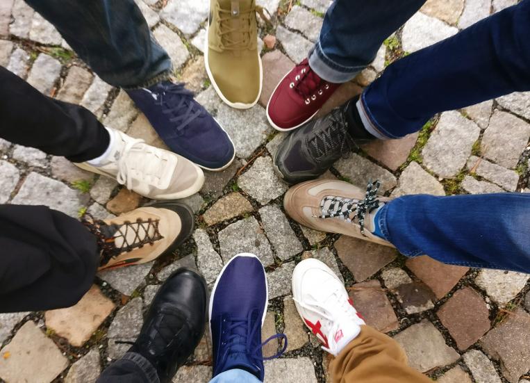 Kuvassa näkyy kymmenen jalkaa. Nuorten jalat ovat ympyrässä siten, että eriväriset kengät muodostavat ympyrän tai tähtikuvion.