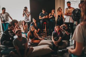 Kuvassa näkyy joukko nuoria miehiä ja naisia. Osa seisoo, osa istuu lattiatyynyillä. Monella on kädessään kamera tai puhelin, jolla he kuvaavat etualalla näkyvää hahmoa, joka puhuu heille.