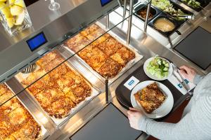 Kuvassa ruokalan älylinjasto. Linjastolla on tarkolla pizzapaloja, ja oikeala näkyy salaattiaineksia. Linjaston yläreunassa annosten yläpuolella on näyttö, josta ruokailija saa lisätietoa valitsemistaan annoksista.