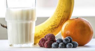 Lasillinen maitoa, banaani ja marjoja.