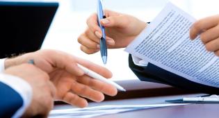 Kuvassa lähikuva kahden henkilön käsistä. Molemmilla on kynä kädessä. Toisen henkilön kädessä on paperi, joka on täynnä tekstiä. Toisen henkilön paperi on pöydällä.