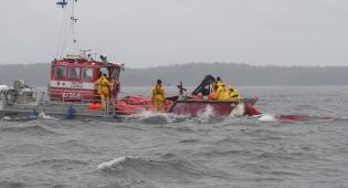 Harmaasävyisessä kuvassa näkyy aallokkoa ja öljyntorjunta-alus, jonka kannella näkyy miehistöä töissä.
