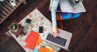 Ylhäällä kuvatussa otoksessa näkyy pöytä, jolla on erivärisiä papereita, kasvi, kännykkä ja läppäri. Pöydän ääressä istuu henkilö, jolla on sylissään muistivihko ja kynä. Hänen toinen kätensä on läppärin näppäimistöllä.