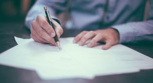 Pöydällä olevien papereiden päällä on kädet, joista toisessa on kynä. Henkilö kirjoittaa paperille.