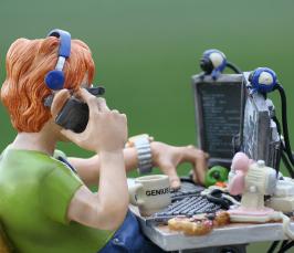 Kuvituskuva, savityö: hahmo istuu pöydän ääressä luurit korvalla ja puhuu kännykkään. Pöydällä on tietokone kahdella näytöllä.