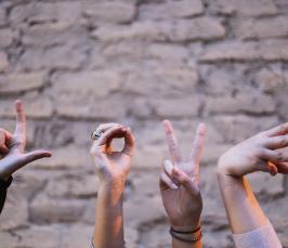 Kuvassa näkyy taustalla tiiliseinä. Etualan alaosasta nousee neljä kättä, joista jokainen muodostaa kirjaimen: L, O, V, E.