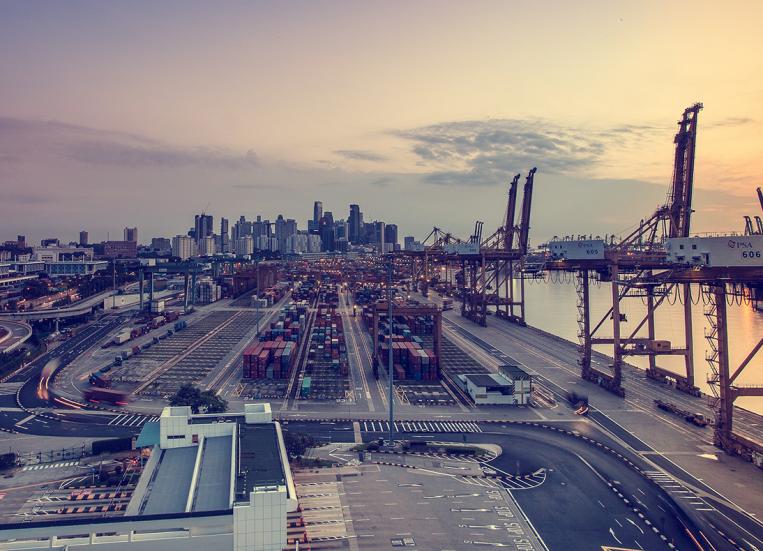 Kuvassa suurkaupungin suuri satama-alue: lastausnostureita, kontteja, rakennuksia. Taustalla näkyy suurkaupungin siluetti.