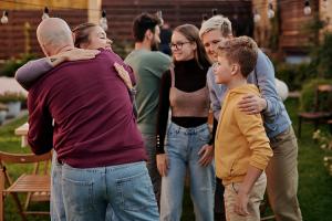 Kuvassa iloisia ihmisiä yhdessä, osa halaa toisiaan.