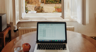 Kuvassa pöytä, jolla läppäri ja vesilasi. Pöydän ääressä istuvalla on näkymä ikkunasta ulos maalaismaisemaan.