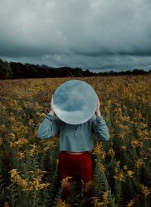 Keltavihreällä kedolla on henkilö, joka pitää päänsä edessään ympyränmuotoista esinettä. Esineestä kuvastuu taustalla näkyvä pilvitaivas.