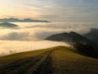 Maisemakuvassa näkyy harjujen huippuja, joista kauimmaisten alaosa on peittynyt pilvien alle. Etualalla näkyy nurmea, ja harjun päällä kulkevalla polulla kaksi kaukaista hahmoa.