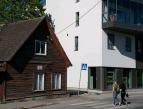 Kuvassa kaksi nuorta ylittää suojatiellä katua. Kadun toisella puolella näkyy vanhan näköinen punainen puutalo, oikealla moderni valkoinen kerrostalo.