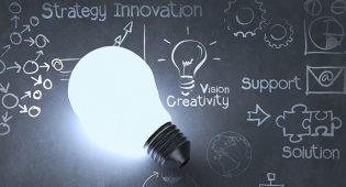 Taustalla näkyy liitutaulu, jossa sanat strategy innovation, vision, creativity, support ja solution. Sanojen vieressä on kaavioita, liitutaulun edessä on valaistu hehkulamppu.