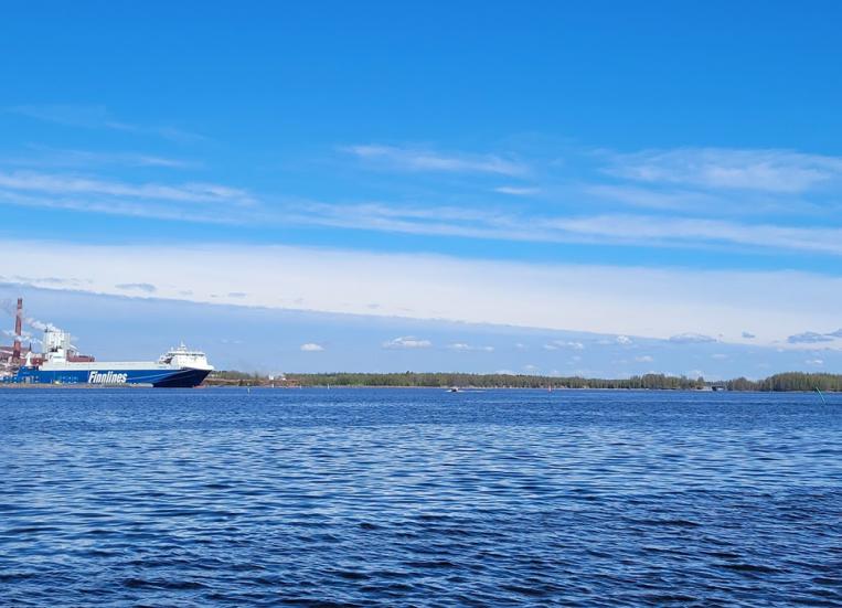 Kuvassa merimaisemaa, taustalla näkyy mannerta, ja vasemmalla kaukana satamassa oleva rahtilaiva.
