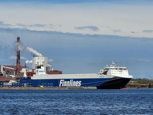 Suuri rahtilaiva satamassa, ympärillä näkyy sinistä merta.