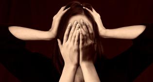 Kuvassa näkyy nainen, jonka kasvot on peitetty käsillä. Naisen päätä ympäröi myös toiset kädet, jotka pitelevät päätä. Kuva kuvastaa häpeän tunnetta ja epätoivoa.