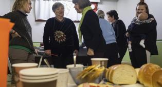 Kuvassa on eri-ikäisiä ihmisiä kahvihuoneessa. Tarjolla on myös pullaa.