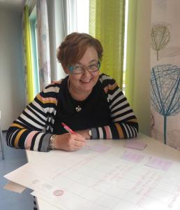 Kuvassa yrittäjä Susanna Sillanpää hymyilee kädessään kynä, pöydällä paljon papereita.
