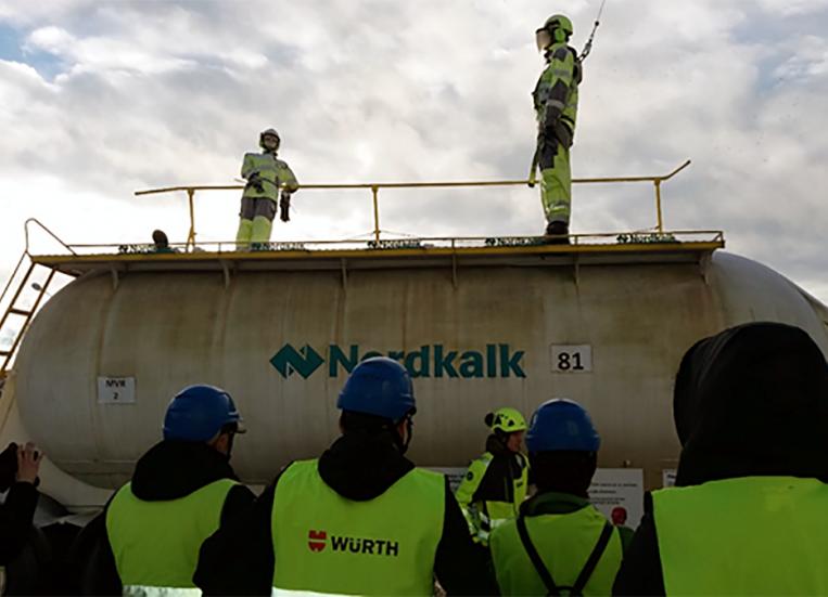 Kuvassa näkyy selin olevia työntekijöitä, joilla on turvaliivit. He katsovat säiliön päälle, jossa kouluttaja opastaa turvavaljaiden käyttöön rakennustyömaalla.