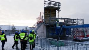 Kuvassa näkyy rakennustyömaa ja työmiehiä turvaliivit päällä.