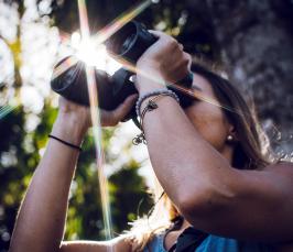 Kuvassa nuori katsoo kiikareilla, taustalta pilkahtaa auringonvalo.