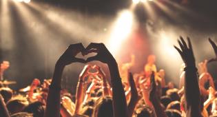 Kuvassa näkymä yleisöstä, joista osalla on kädet ylhäällä. Yhden henkilön kädet muodostavat sydänkuvion. Taustalla näkyy esiintymässä oleva yhtye.