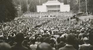 Vanha, mustavalkoinen kuva laulutapahtumasta. Taustalla näkyy esiintymislava, edessä suuri ihmisjoukko.