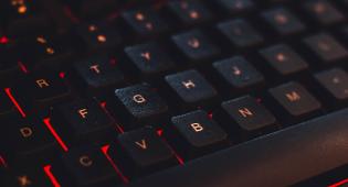 Kuvituskuvassa tietokoneen näppäimistö, jonka taustalla heijastuu punainen väri.