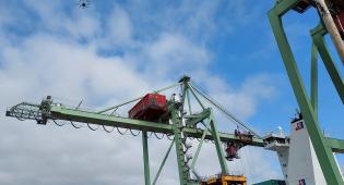 Kuvassa drone lentää korkealla sataman yllä.