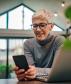 Kuvassa ikääntyvä henkilö katsoo kädessään olevaa älypuhelinta hymyillen. Pöydällä on läppäri.