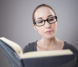 Kuvassa silmälasipäinen nuori henkilö lukee kirjaa.
